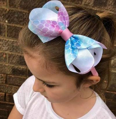 Combed Back Hairstyle With Ponytail And Statement Bow Hair Band On Top